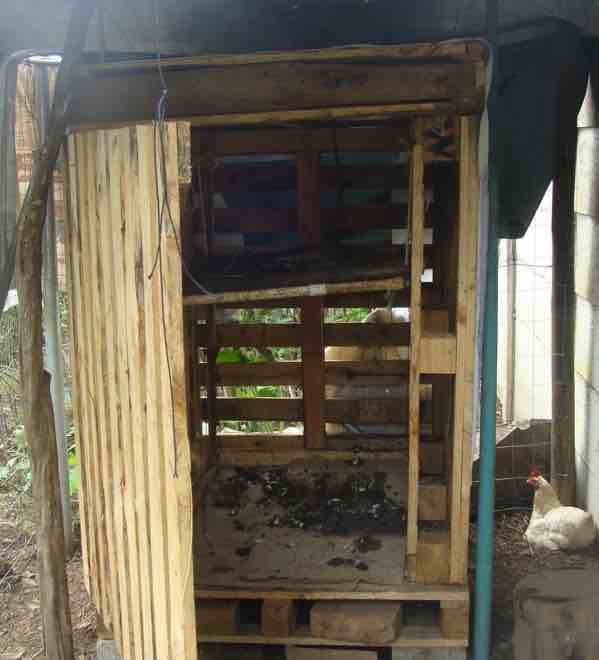A simple chicken coop made from six wooden pallets.