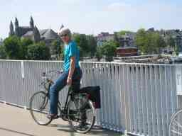 Bernard Preston with his wife cycling over a bridge in Maastricht.