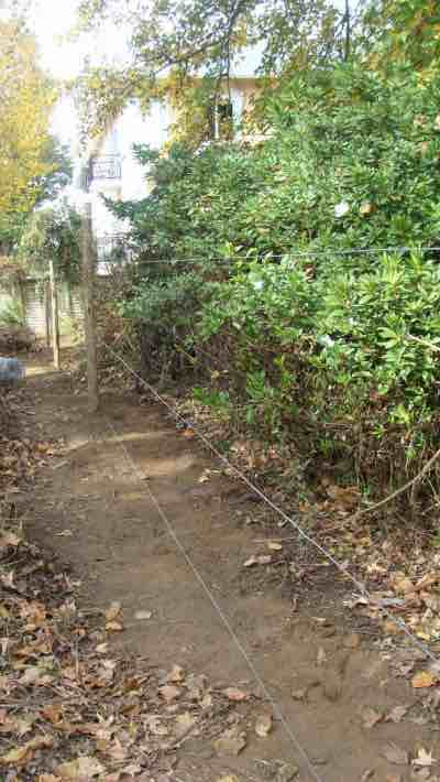 Three tight wires form the structural strength of the vegetable garden fence.