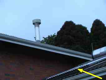 The cowl on chimney pipe of a woodstove, and arrowed the solar water geyser.
