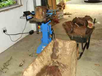 A commercial firewood splitter shown together with a pile of logs.