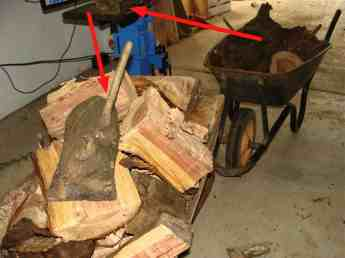 A commercial firewood splitter with a barrow of processed logs ready for stacking.