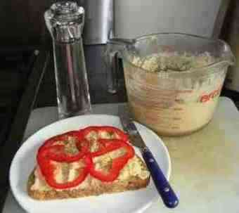 Hummus on a sandwich with red peppers.